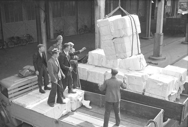 Transferring bales of woodpulp into shed by motor trolley, 3 June 1947